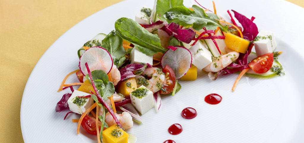 Salada Visconde de Suassuna, camarões cozidos, fios de legumes, queijo coalho e quiabo frito, tudo regado ao azeite de coentro e redução de acerola.